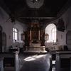 Koret med medeltida dopfunt, altarprydnad från 1600-talet, draperimålningar och basunängel från 1700-talet, votivskepp från 1800-talet och takmålning från 1900-talet.