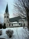 Valdemarsviks kyrka från söder med park i förgrunden.