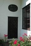 Flyglarnas entréer har ett ovalt fönster med blyinfattade färgade rutor ovan dörren