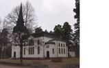 Grycksbo kyrka sedd från sydväst.   En låg mur av sprängd sten avgränsar sedan 1953 kyrktomten mot förbipasserande väg  Digitalfoto Rolf Hammarskiöld