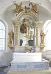 Altaret.  I koret ligger gravhällar och däremellan kalksten. Altaret är murat och vanligen täckt med textilier. Framförvarande altarring är rektangulär till formen, marmorerad i blå och grå toner. Bakom altaret höjer sig en fristående altarprydnad i trä, försedd med rikt förgyllda skulpturer och sniderier. För att få större djup i kyrkorummet är altarprydnaden utformad som en öppen båge mot bakomvarande gravkor, där två marmorsarkofager finns uppställda