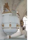 Predikstolen på norra sidan har femsidig korg prydd med kolonner och snidade, förgyllda ornament
