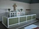 Altarbordet och den tresidiga altarringen har liksom övriga snickerier en enkel och anspråkslös karaktär och är målade med tempera i vitt, grått och olika nyanser av olivgrönt. De väl avstämda kulörerna har alltid stor betydelse i Erskines arkitektur. Altarringen har en stående panel framåt och är genombruten på sidorna.