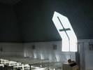 Korsformen i det högt placerade fönstret avtecknar sig effektfullt på motstående vägg.