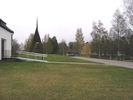 Ånge kyrka med omgivande kyrkogård, del av kyrkan samt klockstapel, vy från väster.